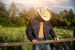 Farmer or cowboy with unbuttoned shirt. Portrait of farmer or cowboy in hat with unbuttoned shirt on muscular torso, looking down, while standing next to hay Royalty Free Stock Photo