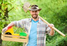 Sexy farmer hold shovel and box with pot. muscular ranch man in cowboy hat. farming and agriculture. Garden equipment royalty free stock photo