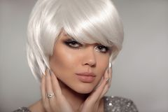 Fashion blond with bob short hairstyle and manicure nail po. Lish. Close up portrait of blonde girl model with white hair presenting diamond ring on finger royalty free stock image