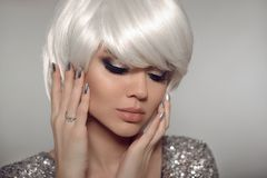 Fashion blond with bob short hairstyle and manicure nail po. Lish. Close up portrait of blonde girl model with white hair presenting diamond ring on finger royalty free stock photo