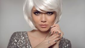 Fashion blond with bob short hairstyle and manicure nail po. Lish. Close up portrait of blonde girl model with white hair presenting diamond ring on finger royalty free stock photos