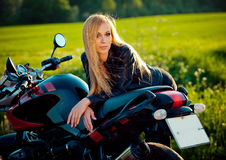 Sexy fashion female biker girl. Blonde woman in leather jacket sitting on vintage custom motorcycle. Outdoors lifestyle Stock Image