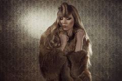 Sexy fashion girl with fur. Cute fashion portrait of attractive young girl posing with long creative hairdo, elegant make-up and wearing winter warm fur Stock Images