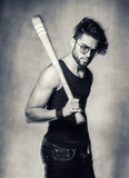 Sexy fashion man model with a baseball bat looking angry against grunge wall Royalty Free Stock Images