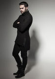 fashion man model in black sweater, jeans and boots posing dramatic Royalty Free Stock Photo
