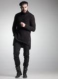 Sexy fashion man model in black sweater, jeans and boots posing dramatic Royalty Free Stock Image