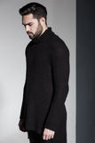 fashion man model in black sweater, jeans and boots posing dramatic Stock Image