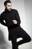 Sexy fashion man model in black sweater, jeans and boots posing dramatic Stock Photography