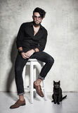 Sexy fashion man model dressed casual posing with a cat against grunge wall Stock Photo