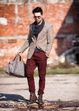 Sexy fashion man model dressed elegant holding a bag Royalty Free Stock Photos