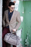 Sexy fashion man model dressed elegant holding a bag posing Stock Image