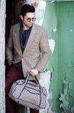 fashion man model dressed elegant holding a bag posing Stock Image