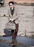 Sexy fashion man model dressed vintage elegant holding a bag posing outdoor Royalty Free Stock Photos