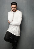 Sexy fashion man model in white sweater, jeans and boots posing dramatic Stock Image