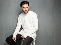 Sexy fashion man model in white sweater, jeans and boots posing dramatic Stock Photo