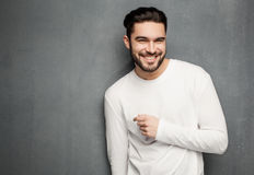 Sexy fashion man model in white sweater, jeans and boots smiling against wall Royalty Free Stock Photos