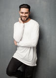 Sexy fashion man model in white sweater, jeans and boots smiling Stock Photo