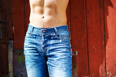 Sexy fashion portrait hot male model in stylish jeans with muscular body posing Stock Photos