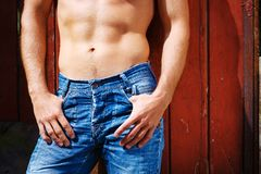 Sexy fashion portrait hot male model in stylish jeans with muscular body posing Royalty Free Stock Photos