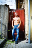 Sexy fashion portrait hot male model in stylish jeans with muscular body posing. Wolves tooth jewelery pendant Stock Photos