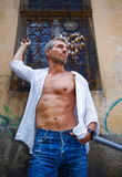 Sexy fashion portrait hot male model in stylish jeans and shirt with muscular body posing. And Dream Catcher Stock Image