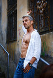 Sexy fashion portrait hot male model in stylish jeans and shirt with muscular body posing. And Dream Catcher Stock Images