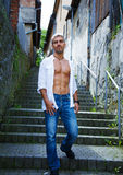 Sexy fashion portrait hot male model in stylish jeans and shirt with muscular body posing. Wolves tooth jewelery pendant Stock Photos