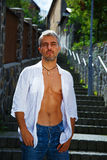 Sexy fashion portrait hot male model in stylish jeans and shirt with muscular body posing. Wolves tooth jewelery pendant Stock Photography