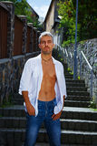 Sexy fashion portrait hot male model in stylish jeans and shirt with muscular body posing. Wolves tooth jewelery pendant Royalty Free Stock Image
