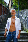 Sexy fashion portrait hot male model in stylish jeans and shirt with muscular body posing. Wolves tooth jewelery pendant, grimace Royalty Free Stock Photography