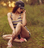 Sexy fashion woman posing sitting on grass Stock Images