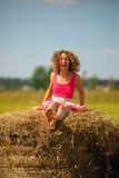Sexy fashion woman in red dress jumps on haystack Stock Images
