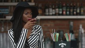 fashionable african american lady in black hat and striped vogue dress drinking cocktail in bar. Hot summer day stock video