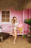 and fashionable model blonde girl with inflatable ice cream in her hands in stylish white swimsuit jumps and posing at the be royalty free stock image