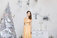 and fashionable model girl with bright makeup, in the long gold dress, posing near the modern silver Christmas tree royalty free stock images