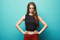 And fashionable model girl with slim sporty figure in black t-shirt, red pants and in stylish round glasses, isolated at gree. N background stock photography