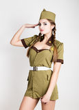 Sexy fashionable woman in military uniform and forage-cap, put a hand to her head, salutes Stock Photography