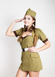 Sexy fashionable woman in military uniform and forage-cap, put a hand to her head, salutes Royalty Free Stock Photo