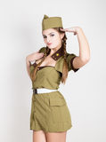 Sexy fashionable woman in military uniform and forage-cap, put a hand to her head, salutes Royalty Free Stock Images
