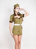 Sexy fashionable woman in military uniform and forage-cap, put a hand to her head, salutes Royalty Free Stock Image