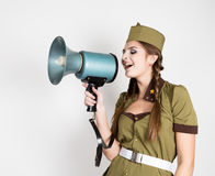 fashionable woman in military uniform and garrison cap, holding bullhorn and screaming Stock Photo