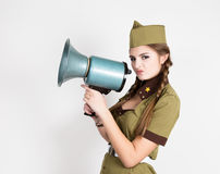 fashionable woman in military uniform and garrison cap, holding bullhorn and screaming Royalty Free Stock Photography