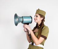 fashionable woman in military uniform and garrison cap, holding bullhorn and screaming Royalty Free Stock Image