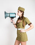 fashionable woman in military uniform and garrison cap, holding bullhorn and screaming Royalty Free Stock Photo