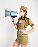 Sexy fashionable woman in military uniform and garrison cap, holding bullhorn and screaming Royalty Free Stock Image