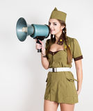 Sexy fashionable woman in military uniform and garrison cap, holding bullhorn and screaming Royalty Free Stock Photos