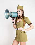 Sexy fashionable woman in military uniform and garrison cap, holding bullhorn and screaming Royalty Free Stock Images