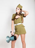 Sexy fashionable woman in military uniform and garrison cap, holding bullhorn and screaming Stock Images