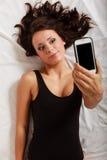 faules Mädchen, das mit Telefon auf Bett im Schlafzimmer liegt Lizenzfreies Stockfoto