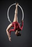 Sexy female acrobat exercising with hanging hoop. In studio Stock Photos